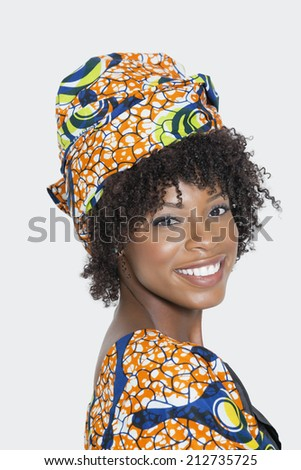 Portrait of young woman in African print attire looking over shoulder against gray background - stock photo