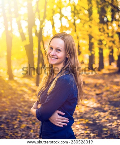 Portrait of young woman in autumn park  - stock photo
