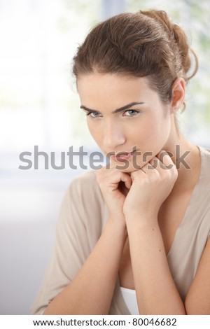 Portrait of young woman in beige, thinking.?