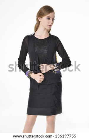 portrait of young woman in black dress standing posing