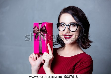 Portrait of young woman in black dress with Christmas gift over grey background
