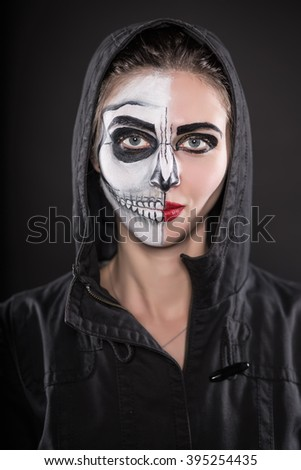 Portrait of young woman in black hood with painted face