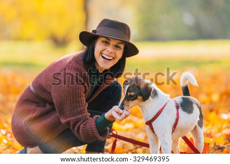 Portrait of young woman in brown hat feeding dog in autumn park - stock photo