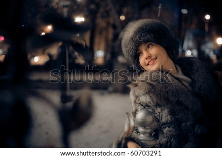 Portrait of young woman in city at night - stock photo