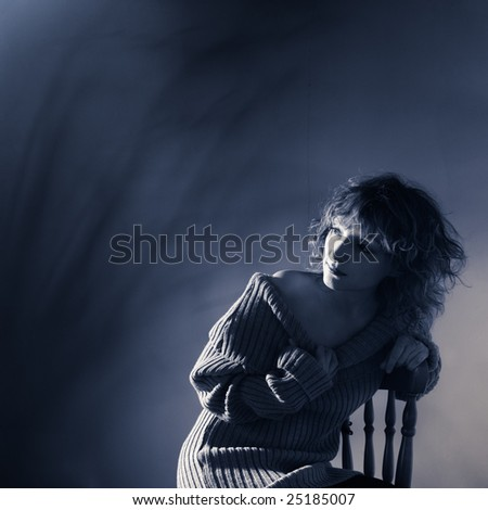 Portrait of young woman in dark blue tones - stock photo