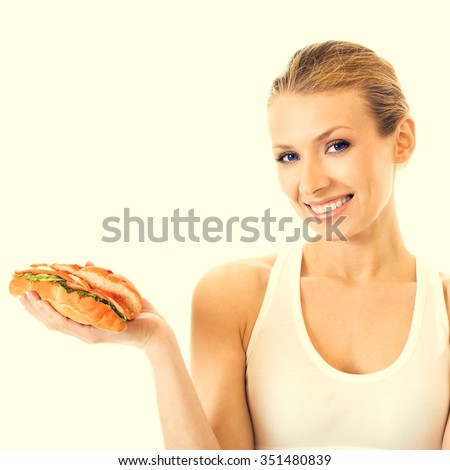 Portrait of young woman in fitness wear with sandwich, beauty and healthy eating concept - stock photo