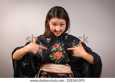 Portrait of young woman in kimono pointing at herself with disbelief. You think it was me?! - stock photo