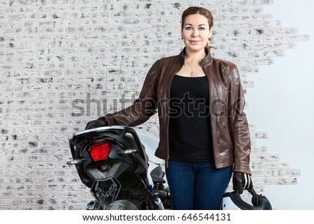 Portrait of young woman in leather jacket stands near motorcycle, holds helmet in hands, brick wall of garage box