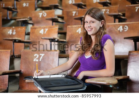 Portrait of young woman in lecture hall writing in binder - stock photo