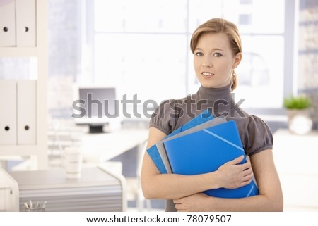 Portrait of young woman in office, holding file folders. Looking at camera, smiling.? - stock photo