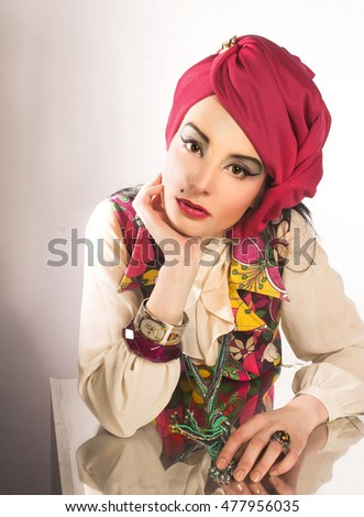 Portrait of young woman in pink turban and in vintage dress.