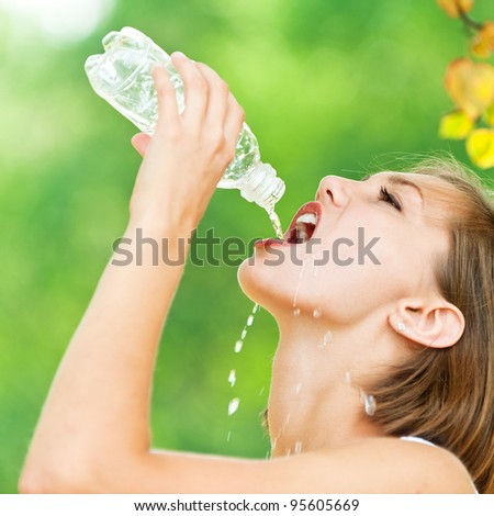 portrait of young woman in profile with short hair quenches thirst (drinks from bottle of water), against backdrop of summer nature - stock photo