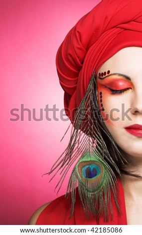 Portrait of young woman in red turban with peacock plume - stock photo