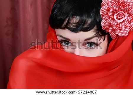 Portrait of young woman in red veil on her face and red background.