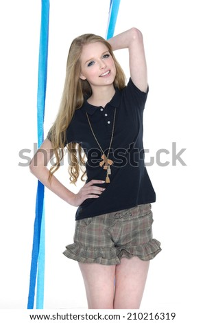 portrait of young woman in shorts posing with blue ribbons on white background