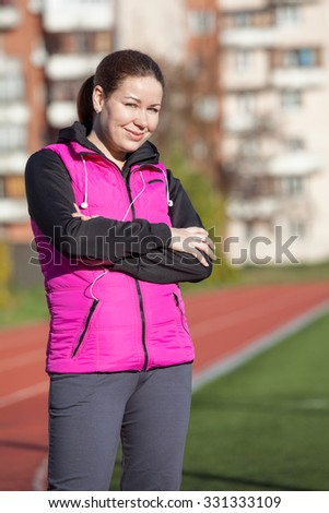 Portrait of young woman in sport wear at the stadium ready for jogging - stock photo