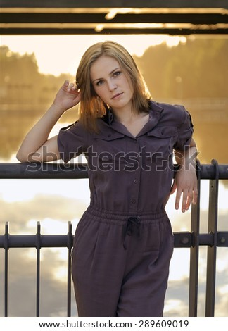 Portrait of young woman in stylish overalls - stock photo