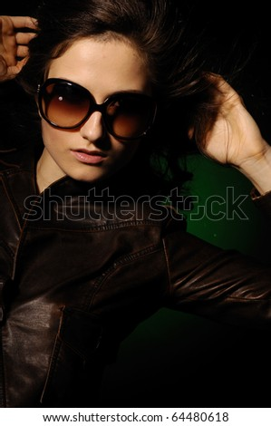 portrait of young woman in sunglasses on black