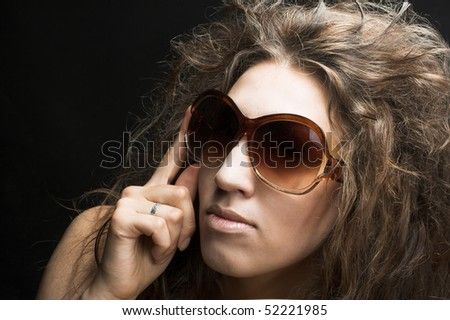 Portrait of young woman in sunglasses on the dark background
