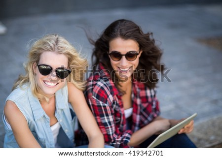 Portrait of young woman in sunglasses using digital tablet - stock photo