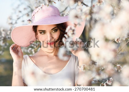 Portrait of young woman in the flowered field in the spring time. Almond flowers blossoms. Girl wearing white dress and pink sun hat - stock photo