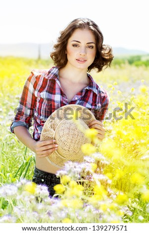 Portrait of young woman in the flowers field - stock photo