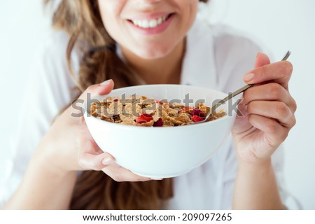 Portrait of young woman in underwear eating cereals. Isolated on white. - stock photo