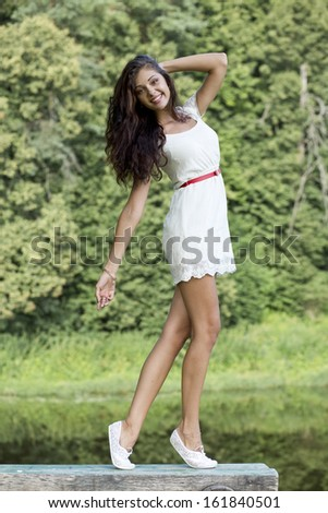 Portrait of young woman in white dress - stock photo