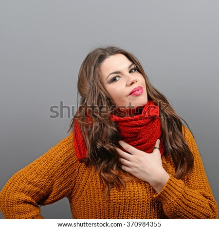 Portrait of young woman in winter clothes against gray background