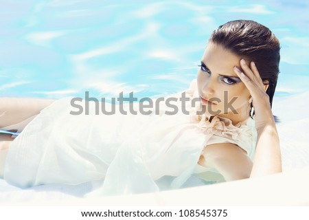 portrait of  young woman inside a swimming pool, wearing a  dress