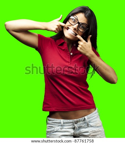 portrait of young woman joking against a removable chroma key background - stock photo