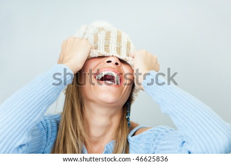 portrait of young woman laughing while covering face with wool hat. Horizontal shape, Copy space - stock photo
