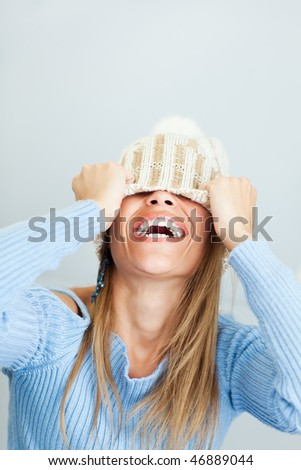 portrait of young woman laughing while covering face with wool hat. Vertical shape, Copy space - stock photo