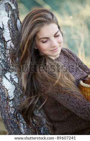 Portrait of young woman leaning against a tree in autumn. - stock photo