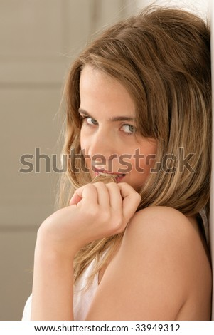 Portrait of young woman leaning on wall with hair wisp in mouth - stock photo