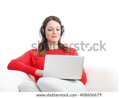 Portrait of young woman listening music while sitting at sofa and using laptop. Isolated on white background. - stock photo