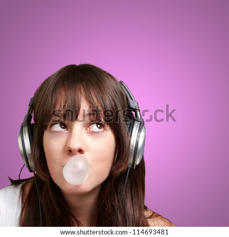 portrait of young woman listening to music with bubble gum over purple - stock photo