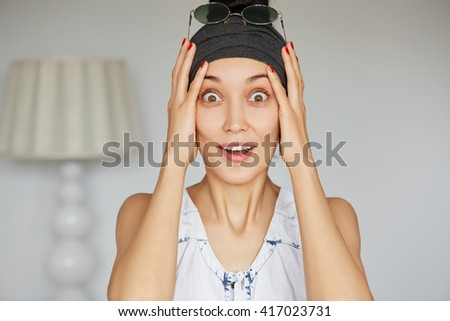 Portrait of young woman looking at the camera, stunned with big sale prices or some sensational news, holding her head in astonishment with eyes wide open posing against white home interior background - stock photo