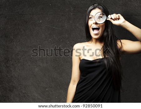 portrait of young woman looking through a magnifying glass against a grunge wall - stock photo