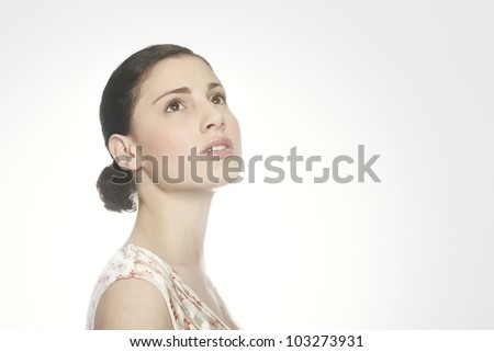 Portrait of young woman looking up on a white background, backlit.