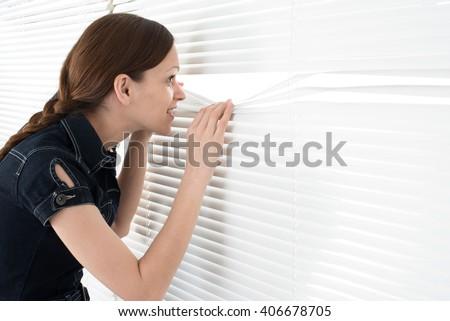 portrait of young woman looks through jalousie - stock photo