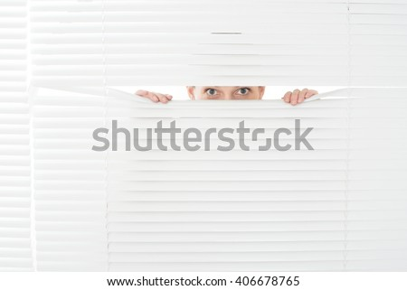 portrait of young woman looks through jalousie