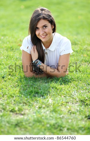 Portrait of young woman lying on a green lawn