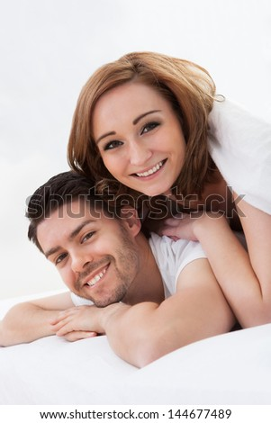 Portrait of young woman lying on husband's back