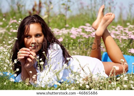 Portrait of young woman lying on the grass - stock photo