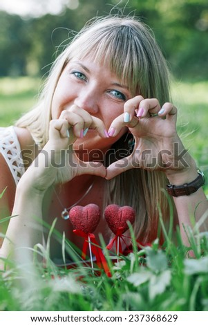 portrait of young woman lying on the green grass, showing heart sign  - stock photo