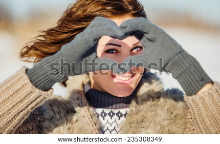 Portrait of young woman making heart symbol with hands  - stock photo