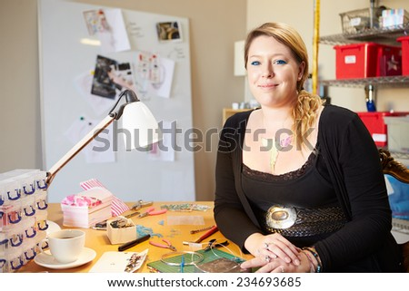 Portrait Of Young Woman Making Jewelry At Home - stock photo