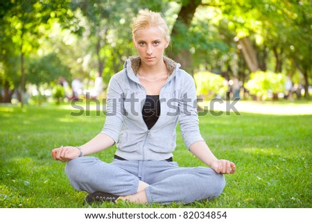 Portrait of young woman meditating in pose of lotus on green grass on meadow at summer park under tree - stock photo
