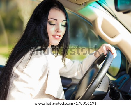Portrait of young woman model sitting in a car - stock photo